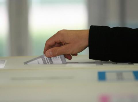 Un elettore che inserisce la scheda in un'urna elettorale
